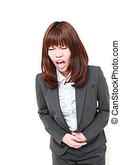 young Japanese businesswoman suffers from stomachache -...