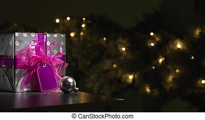 Purple Christmas gift with a tree in the background