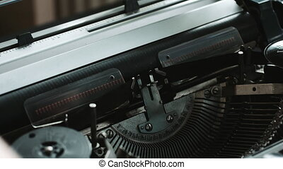 Man loads a blank sheet of paper in the typewriter -...