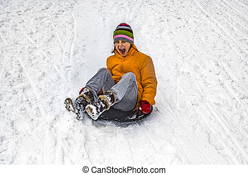 girl haas fun sledging down the snowy hill in winter