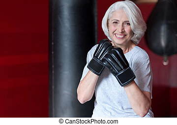 Fanny smiling gray haired woman preparing to boxing. - Come...