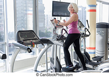 Emotional smiling gray haired woman training having fitness....