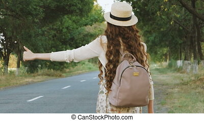 Girl with hat and backpack hitchhiking on the road -...