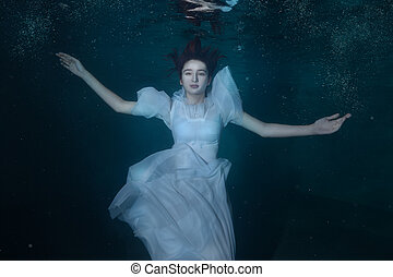 Woman in a white dress under water. - Woman in white dress...