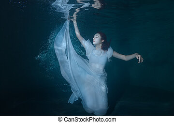 Woman on the ocean floor. - Woman under water on a blue...