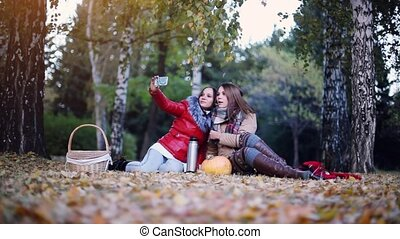 Beautiful girls making selfie on a picnic in autumn park sitting on the fallen leaves near the pumpkin at halloween time. 1920x1080