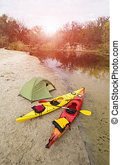 Camping on the beach. - Traveling by kayak on the river on a...