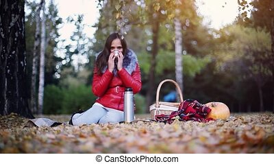 Young beautiful woman sitting has picnic drinking hot tea...