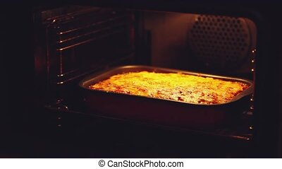 Baked lasagna in the oven. Open the oven to get the...