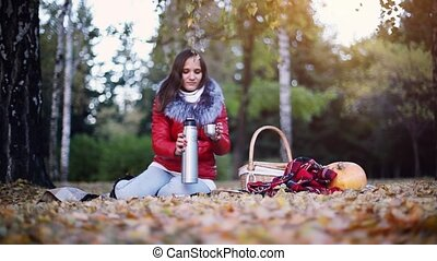 Young woman sitting has picnic drinking hot tea from a...