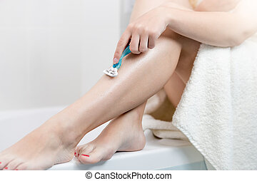 Young woman covered in bath towel shaving legs with razo -...