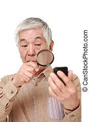 senior Japanese man with presbyopia - studio shot of senior...