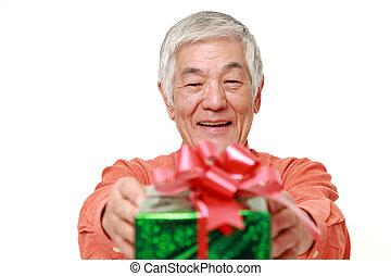 senior Japanese man offering a gift - studio shot of senior...