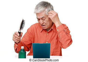 senior Japanese man using hair restorer - studio shot of...
