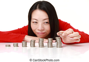 woman put coins to stack of coins - concept shot of Japanese...