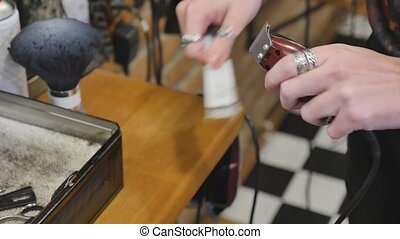 Hands of a man with a vintage barber electric clippers for beard and hair. Profession barber, hairdresser