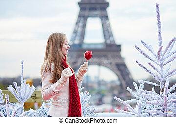 Girl with caramel apple on a Parisian Christmas market near...