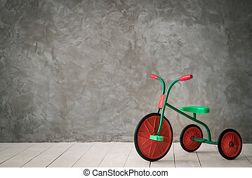 Retro children tricycle against concrete wall