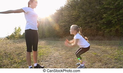 Mom and daughter are engaged in fitness outdoors