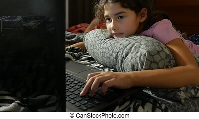 little girl playing child in the notebook online game laptop...
