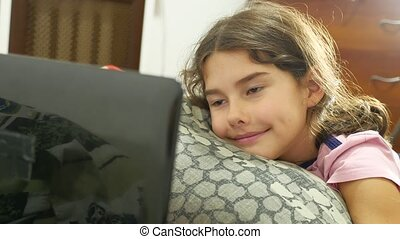 little girl playing in the notebook online game laptop -...