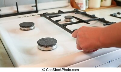 woman washes a gas stove cleaning in the kitchen - woman...