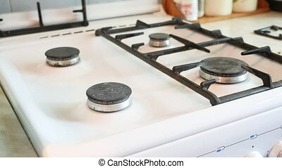 woman washes a gas stove in cleaning the kitchen