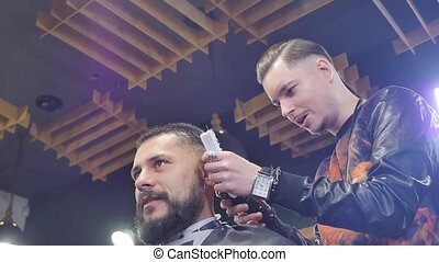 Making hair look magical. Young bearded man getting haircut with straight edge razor by hairdresser while sitting in chair at barbershop
