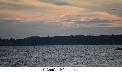 Silhouette of two persons in motor boat at dawn on river or...