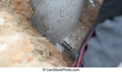 drilling a hole in a concrete well in trench - Closeup of...