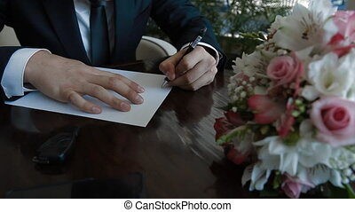 Groom start writing a paper letter to his bride. Weddong...