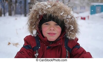 Boy catches snowflakes mouth