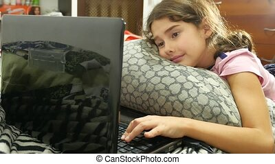 little child girl playing in the notebook online game laptop