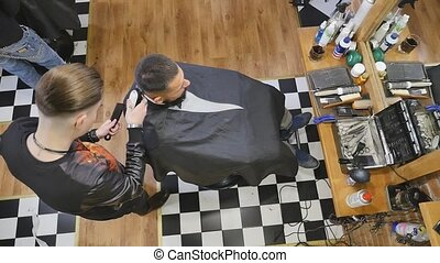Client during beard and moustache grooming in barber shop.