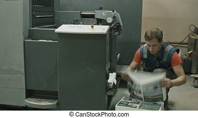 Printing process - worker inserts paper sheets, wide angle