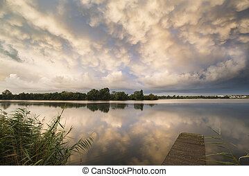 Stunning dramatic mammatus clouds formation over lake...