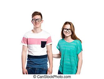 Teenage boy and girl wearing eyeglasses. Studio shot,...