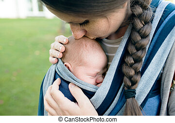 Beautiful mother kissing her son in sling, green nature -...