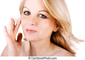 Woman applying face cream - A beautiful middle aged woman...