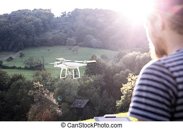 Unrecognizable hipster man with flying drone. Sunny nature....