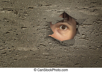 Eye looking through a hole in wall.