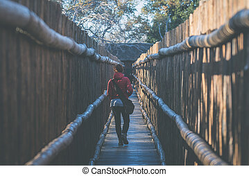 Woman walking in wooden narrow walkway. Protection for...