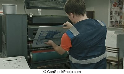 Worker pulls on the blank printable on polygraph industry...