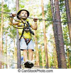 little cute boy in helmet runs track in forest