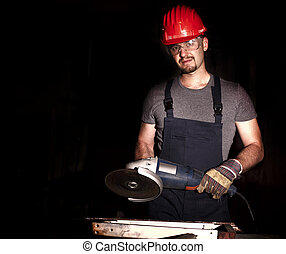 manual worker with grinder and dark background