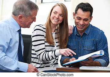 Couple With Financial Advisor Studying Document In Office