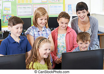 Elementary School Pupils With Teacher In Computer Class