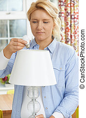 Woman Putting Low Energy LED Lightbulb Into Lamp At Home