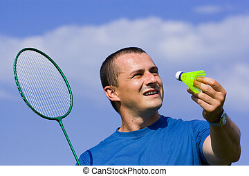 Young man playing badminton in a sunny day