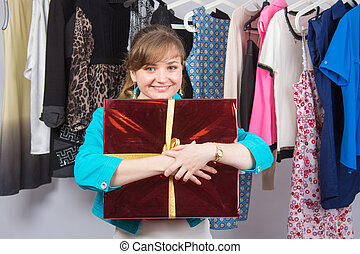 Happy young girl standing with big red gift on background of...